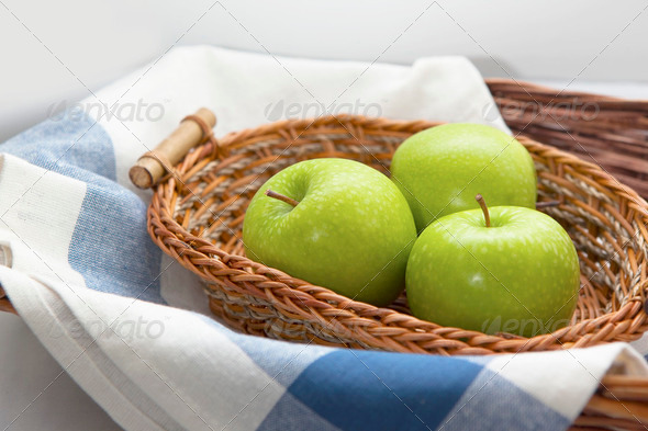 Green apples in the brown wicker basket - Stock Photo - Images
