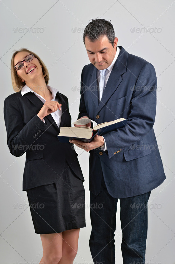 Beautiful business woman with male colleague reading a book - Stock Photo - Images