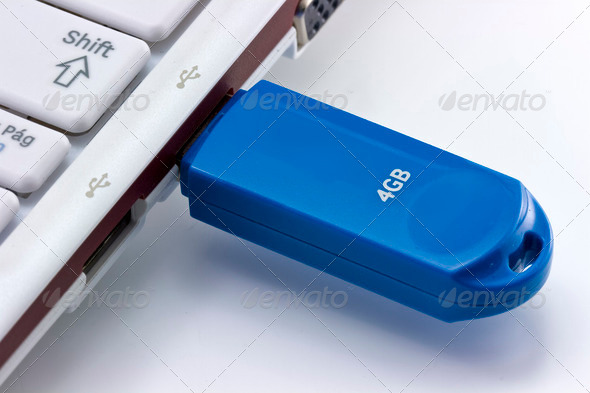 Laptop and flash pen drive arranged on table - Stock Photo - Images