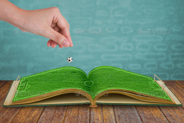 Hand drop football down to green grass  book of soccer stadium - Stock Photo - Images