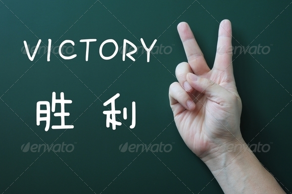 Victory gesture on a blackboard background - Stock Photo - Images