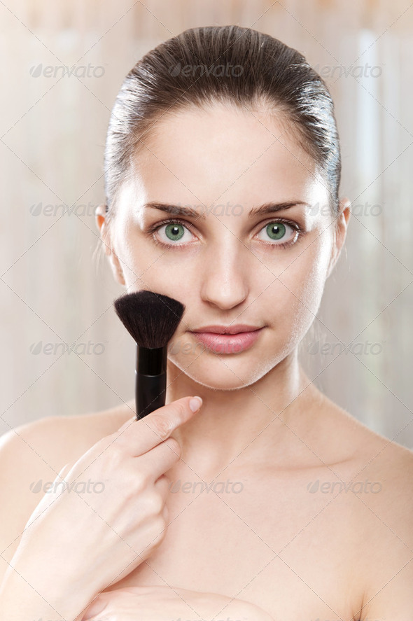 Green eyed model with make-up brush - Stock Photo - Images