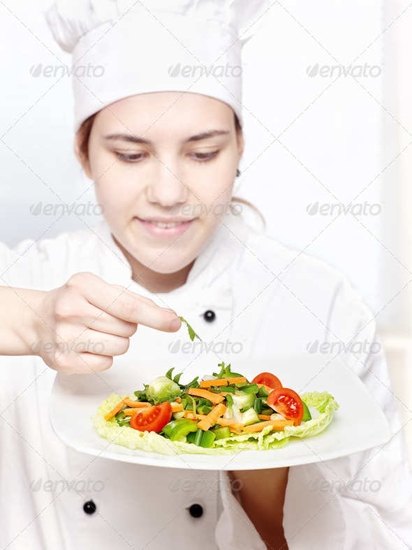young chef decorating delicious salad - Stock Photo - Images