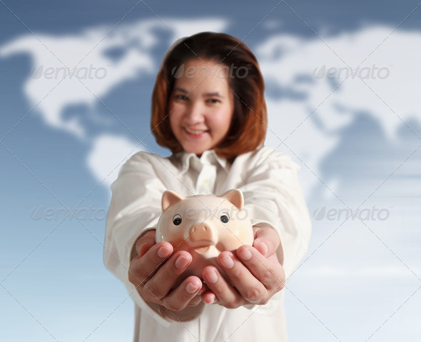 Smiling woman holding piggy bank - Stock Photo - Images