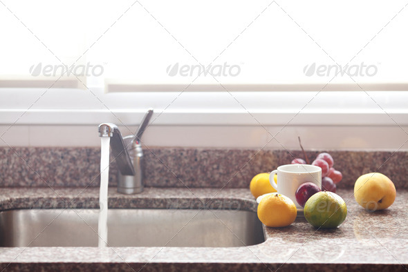 cup, fruits and faucet on the kitchen - Stock Photo - Images