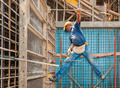Construction worker balancing between scaffold and formwork fram - PhotoDune Item for Sale