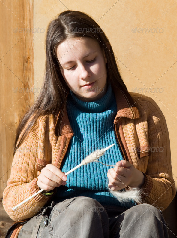 Girl spins a yarn of wool - Stock Photo - Images