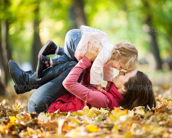 Woman with child having fun in autumn park - Stock Photo - Images