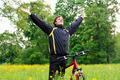 Excited happy man cyclist with hands outstretched embracing vitality freedom