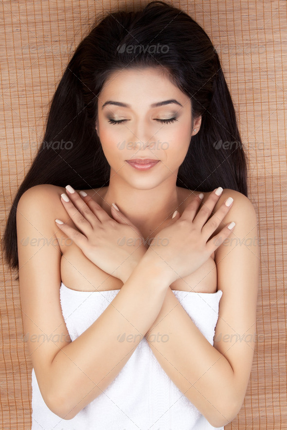 portrait of young woman at a spa, lying on her back, smiling, cl - Stock Photo - Images