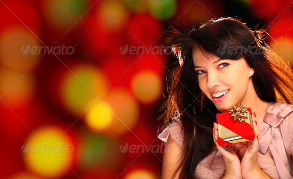 Portrait of a woman holding a gift - Stock Photo - Images