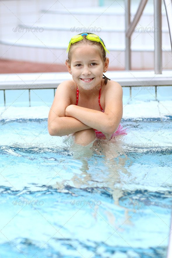 Child relaxing by swimming pool - Stock Photo - Images