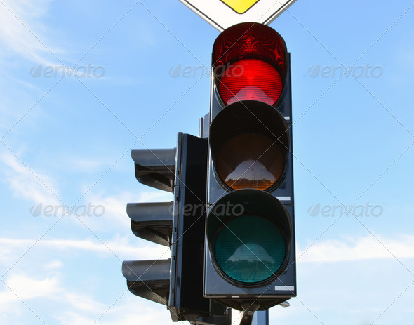 Red color traffic light blue sky in background - Stock Photo - Images