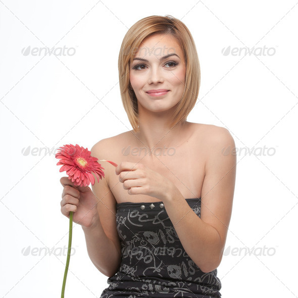 portrait of a young woman picking pettals from a flower, looking - Stock Photo - Images
