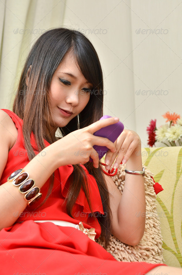 Portrait of young beautiful smiling woman wearing with her mobile phone on sofa  - Stock Photo - Images