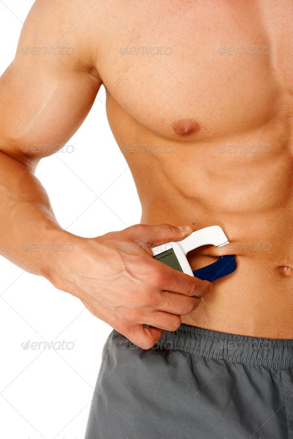 Sporty man measures level of fat on his body - Stock Photo - Images