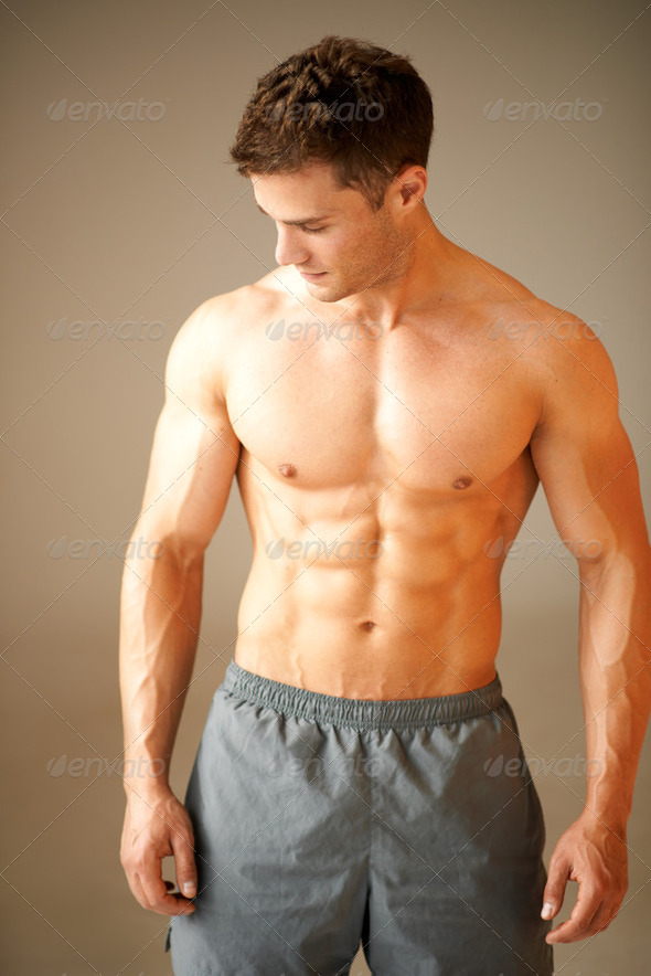 Portrait of muscular sporty man standing on brown - Stock Photo - Images