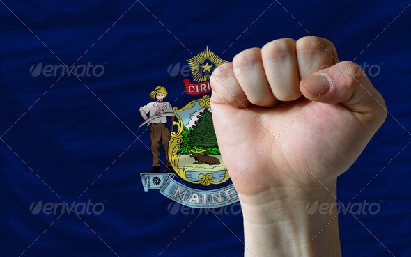 us state flag of maine with hard fist in front of it symbolizing - Stock Photo - Images