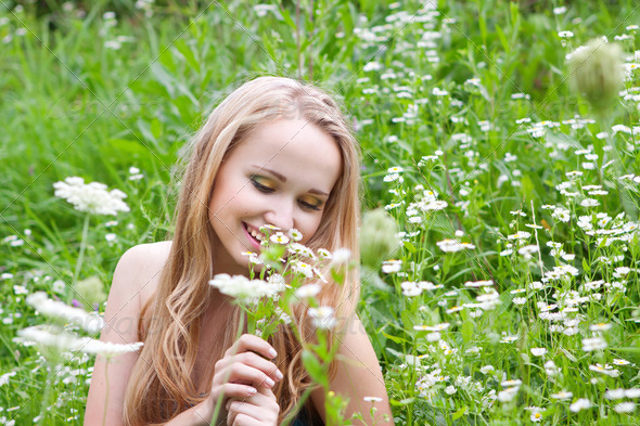 young girl in a meadow with camomiles - Stock Photo - Images