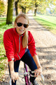 Happy woman cycling on bicycle, autumn