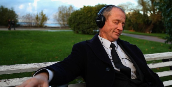 Senior Businessman Enjoying Music Outdoors