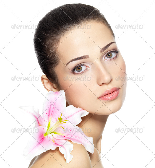 Beauty face of young woman with flower. Beauty treatment concept - Stock Photo - Images