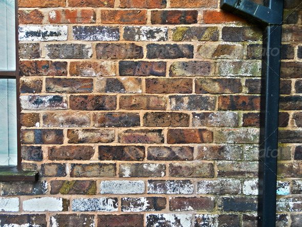 Urban brick wall with window and metal tube - Stock Photo - Images