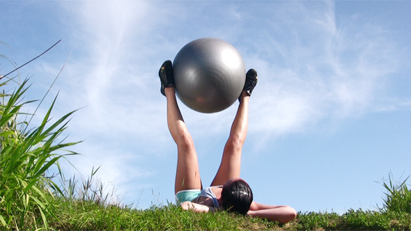 Young Woman Exercising With Ball