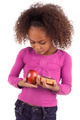 Little African Asian girl hesitating between fruits or  candy - PhotoDune Item for Sale