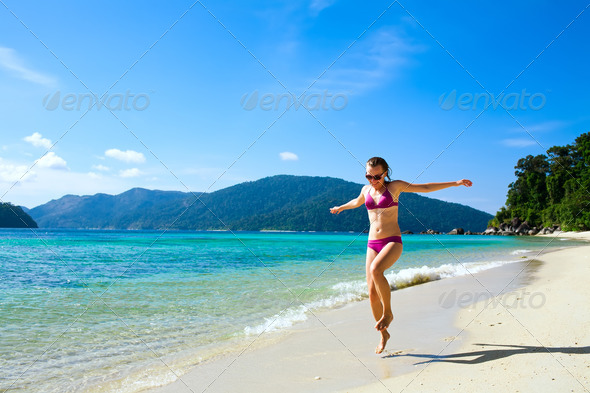 Woman running along tropical island beach - Stock Photo - Images