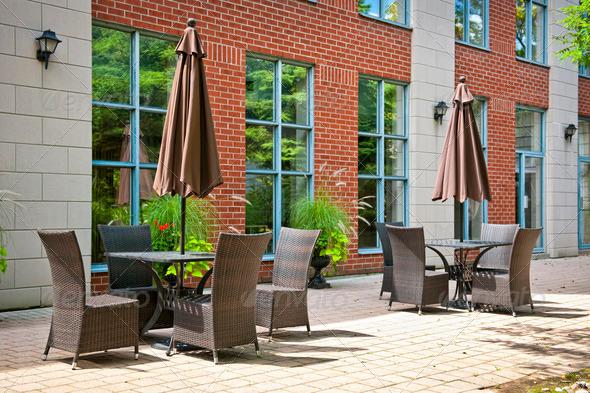 Patio furniture with umbrellas on stone patio near upscale condo building