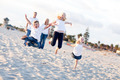 Happy Sibling Children Jumping for Joy at the Beach as Parents Watch.