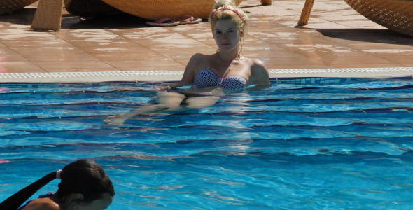 Blonde Girl Relaxing Near The Pool