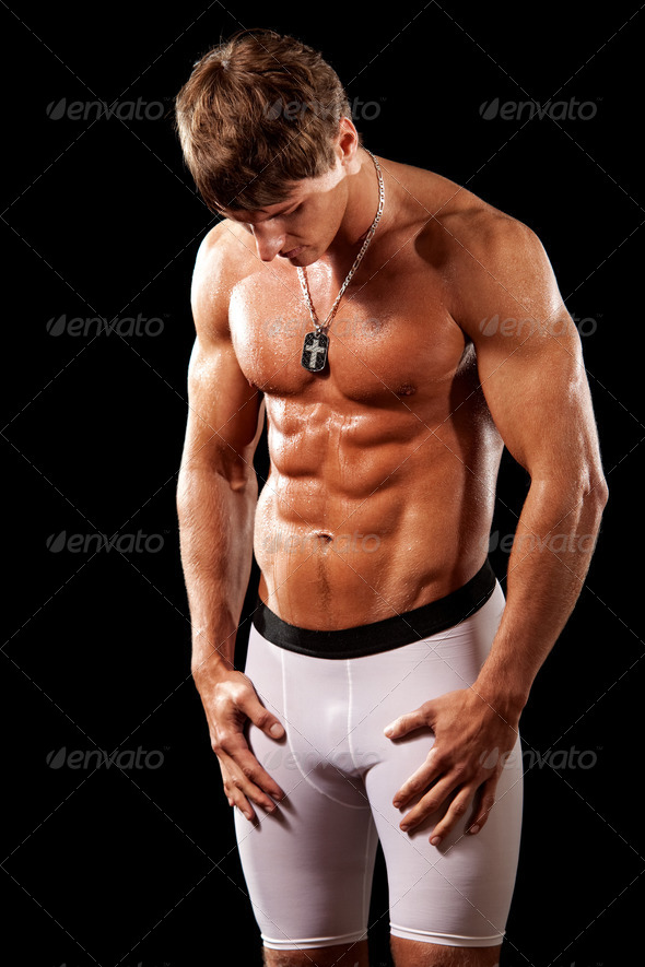 Male bodybuilder posing. Studio shot over black. - Stock Photo - Images
