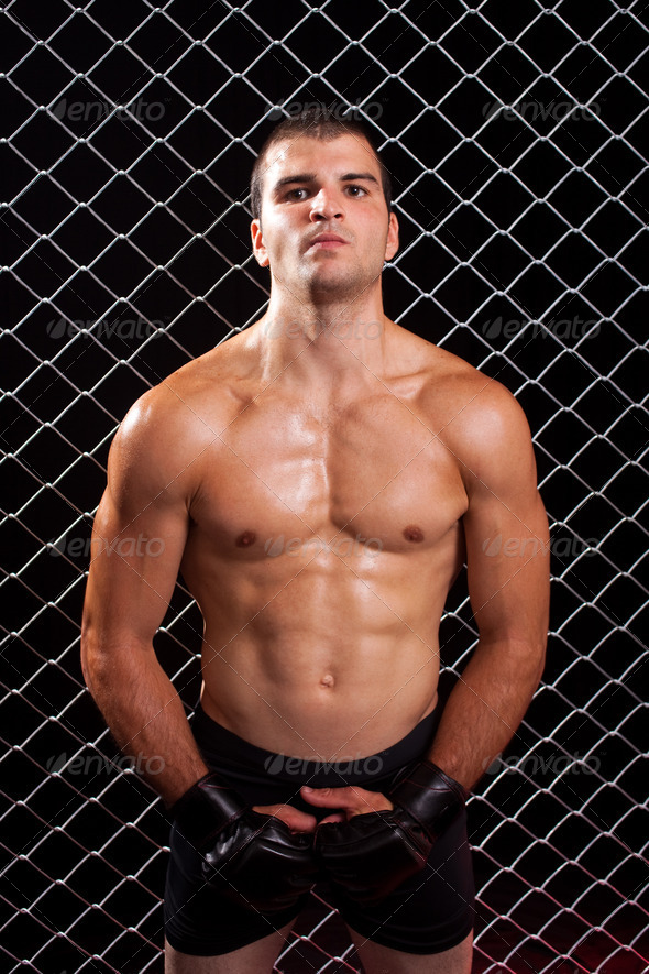 Mixed martial artist posed in front of chain link - Stock Photo - Images