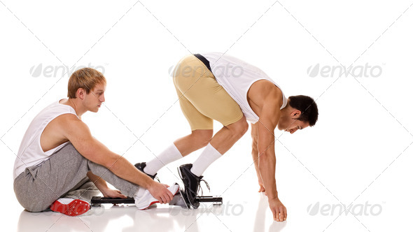 Track and field athlete at start of sprint. Studio shot over white. - Stock Photo - Images