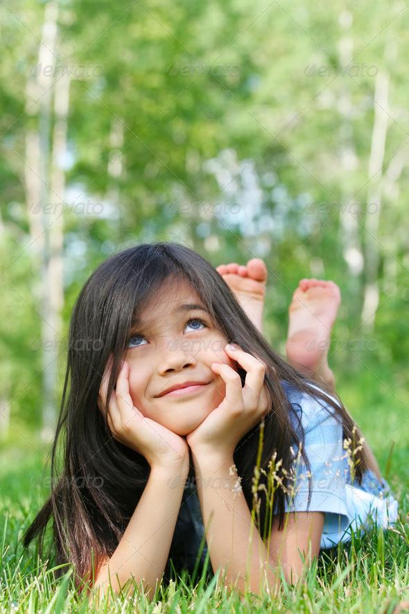 PhotoDune Little biracial girl lying on grass thinking 3675680