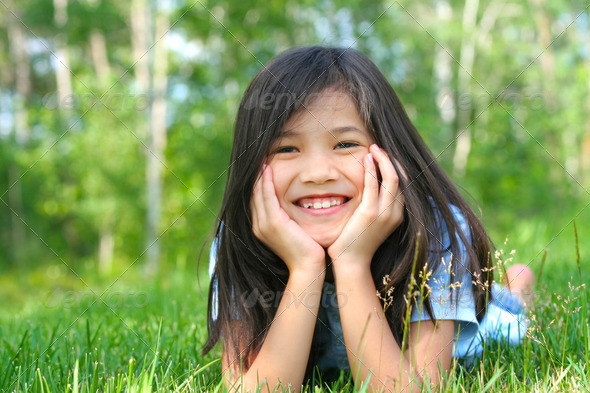 PhotoDune Child lying on grass with head on hands smiling 3675683