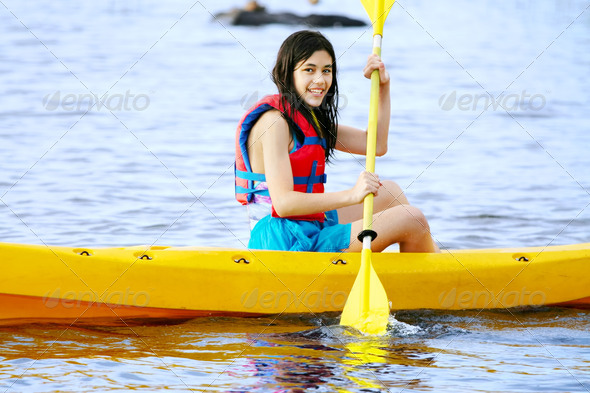 PhotoDune Teen girl in yellow kayak on lake 3675685