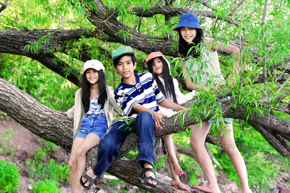 PhotoDune Four children sitting on large tree branch 3675688