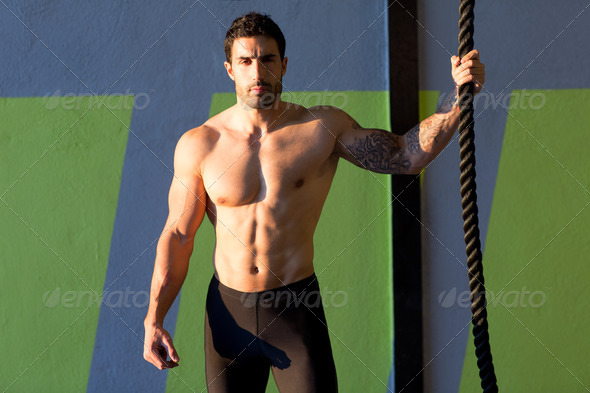 Crossfit gym man holding hand a climbing rope - Stock Photo - Images