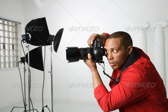 Man photographing in studio - Stock Photo - Images