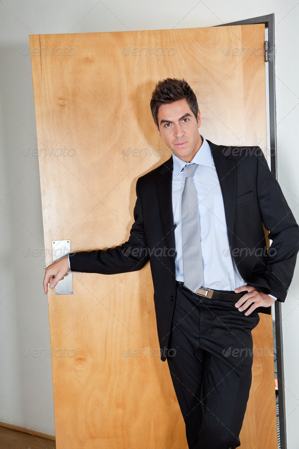 Young Businessman Standing With Hand On Hip - Stock Photo - Images