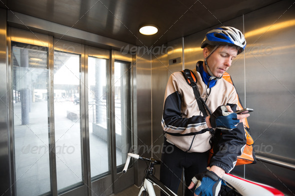 Male Cyclist With Courier Bag Using Mobile Phone In An Elevator - Stock Photo - Images