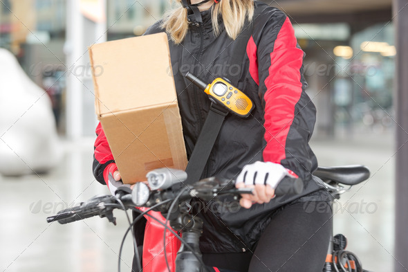 Female Cyclist With Cardboard Box And Courier Bag On Street - Stock Photo - Images