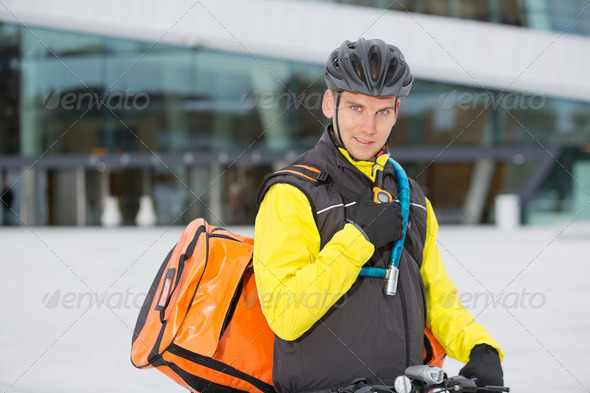 Cyclist With Courier Delivery Bag Using Walkie- Talkie - Stock Photo - Images