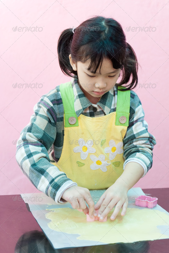 Asian kid making cookies - Stock Photo - Images