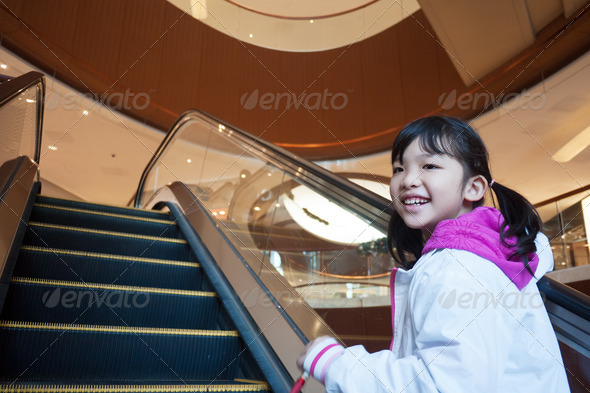 Asian kid taking escalator - Stock Photo - Images