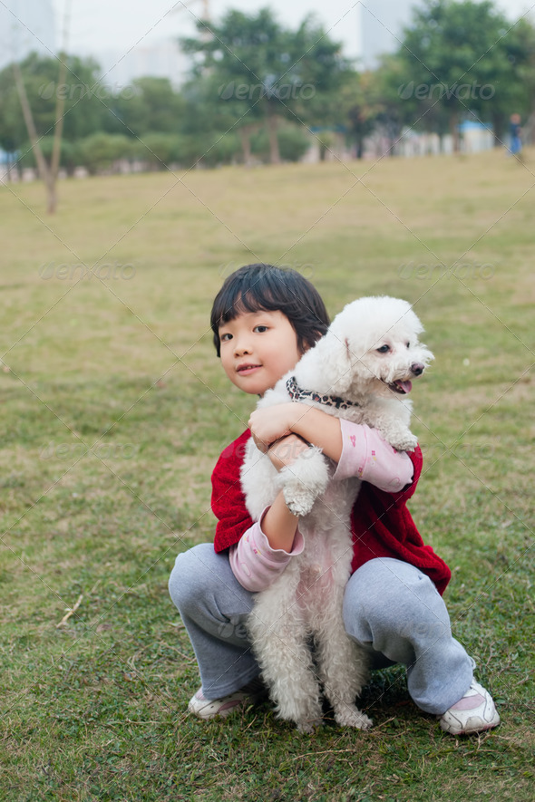 Asian kid holding dog - Stock Photo - Images