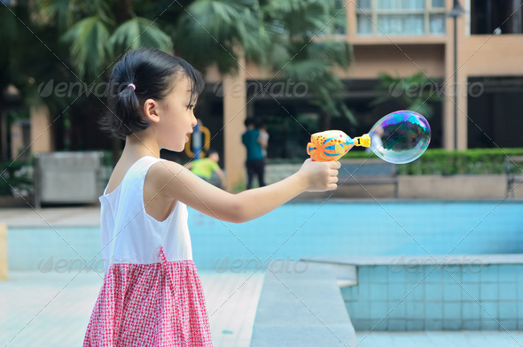 Asian kid blowing bubble - Stock Photo - Images